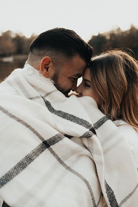 a couple snuggling under a cute blanket