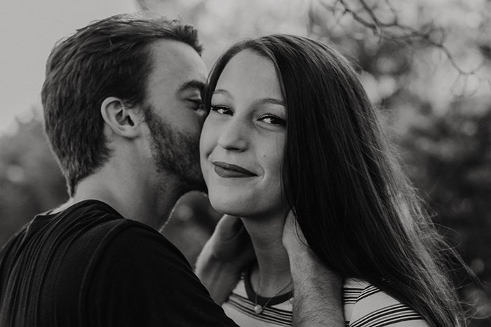 black and white portrait of a man kissing his smiling girlfriend