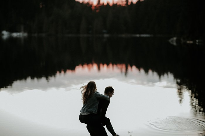 a man giving a woman a piggy back in front of a lake