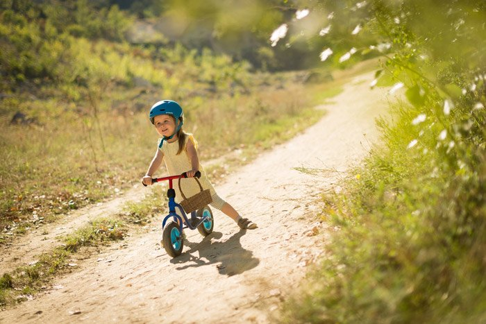 Photo of a little girl with a small bicycle on a dirt road