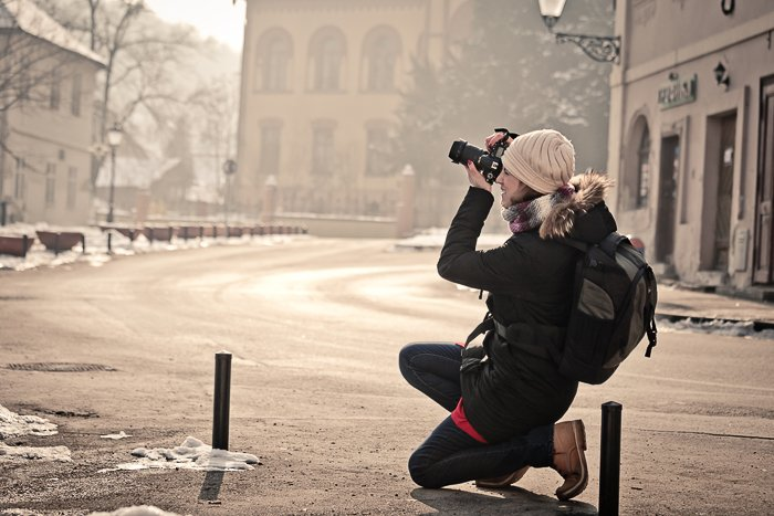 a female photographer shooting a street scene on a DSLR