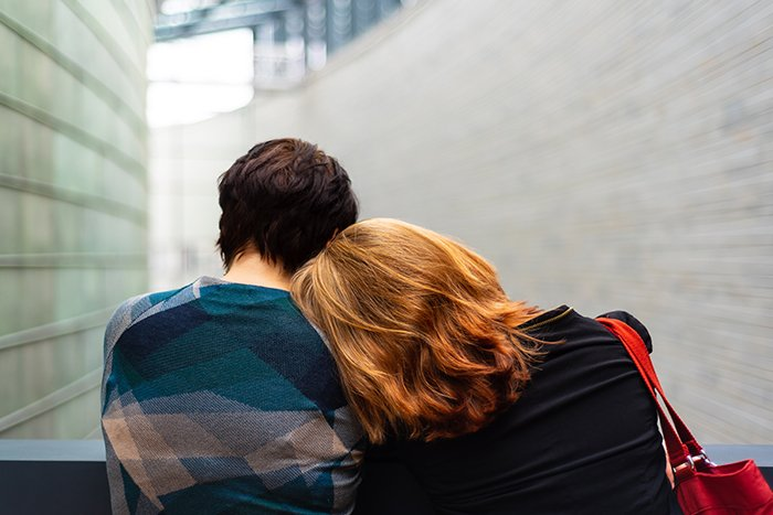 a portrait of the back of two women leaning on each other