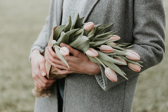 a close up of a person holding flowers at a funeral