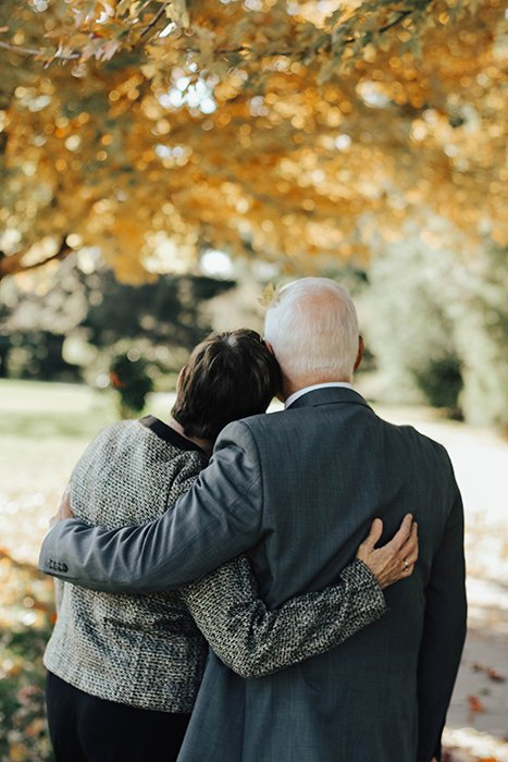 the back of an elderly couple at a funeral