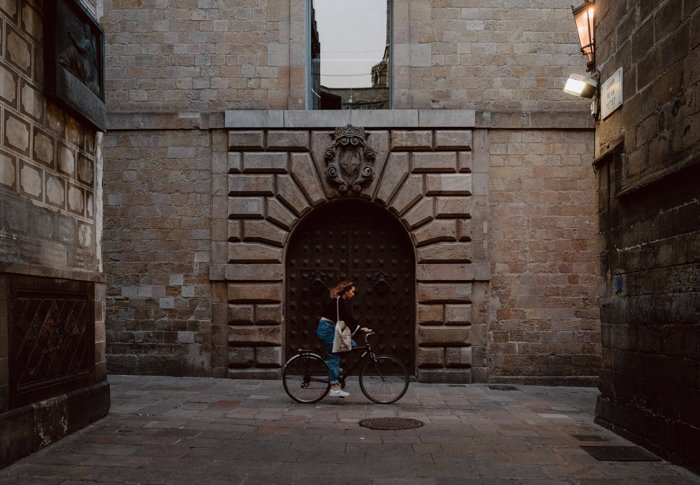 Photo of a woman riding a bike on the street
