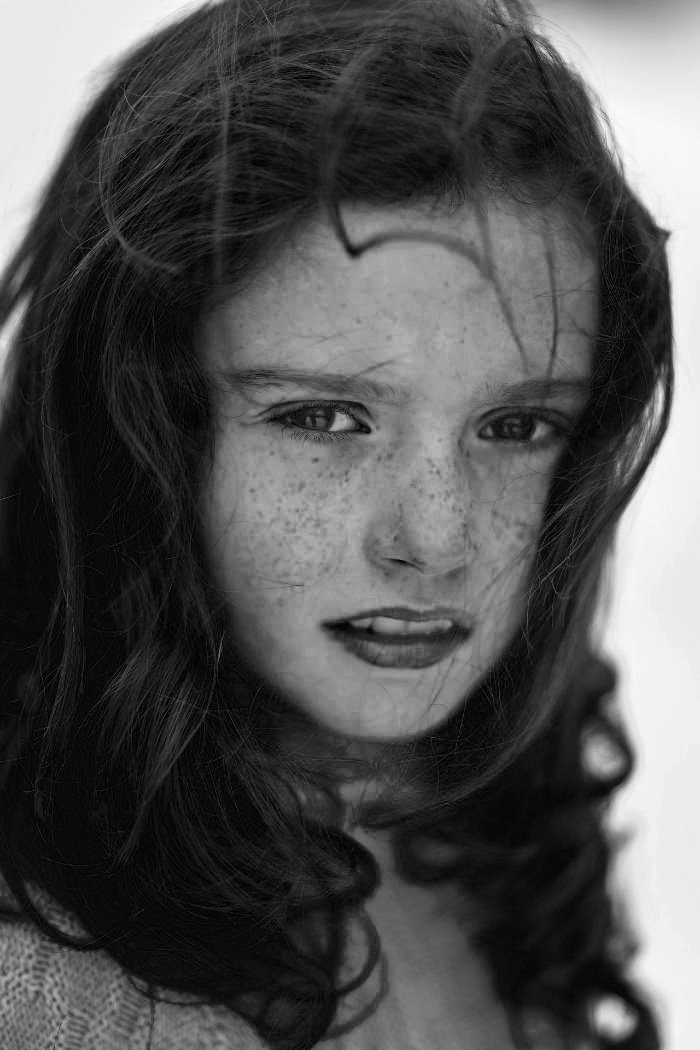 Black and white portrait photo of a girl with freckles
