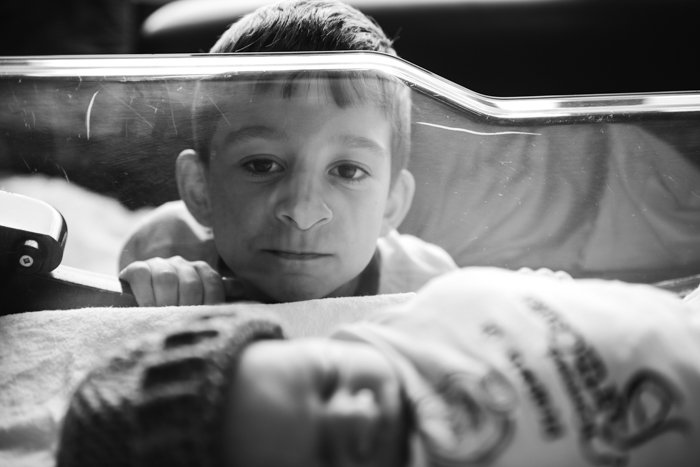 Photo a child watching his brother sleeping in a crib