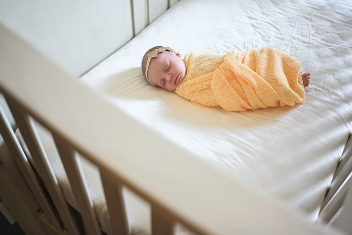 Photo of a baby sleeping in a yellow blanket