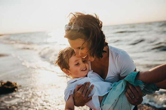 a sweet mommy and me photoshoot of a mother and young son playing on the beach