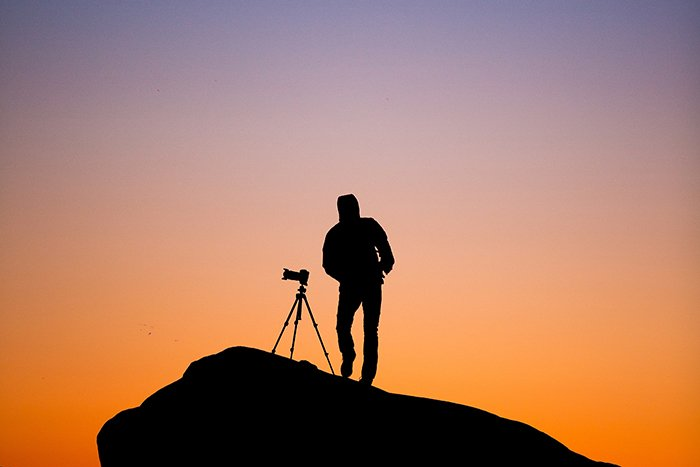 Silhouette of a man standing on a cliff with a tripod