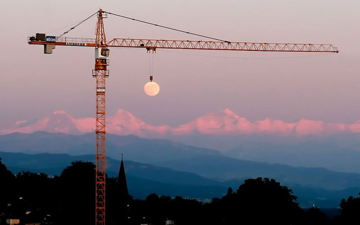 Photo of a crane holding the moon in the background