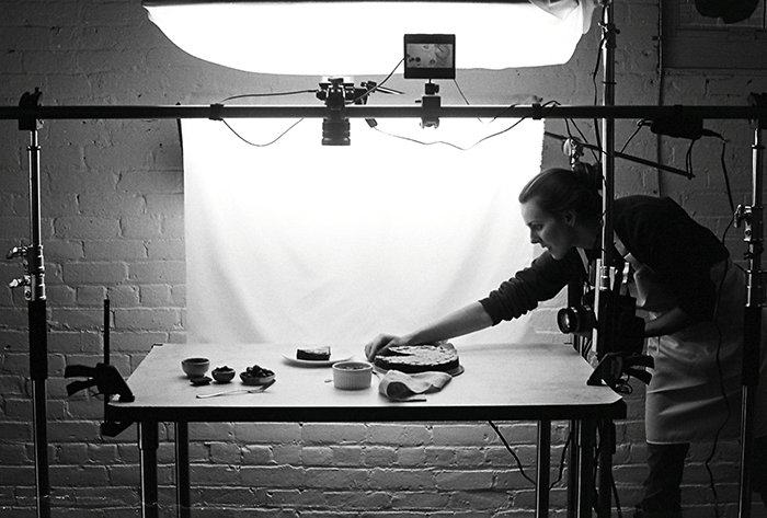 Photo of a photographer setting the composition for food photography