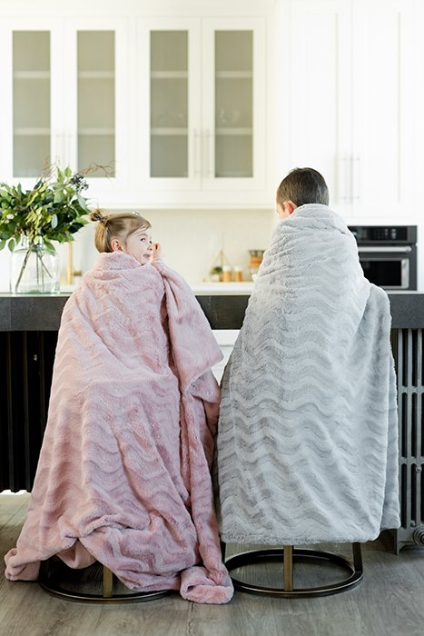 Two small children sitting in the kitchen wrapped in blankets