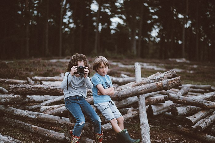 Photo of kids sitting on logs taking photos with a camera