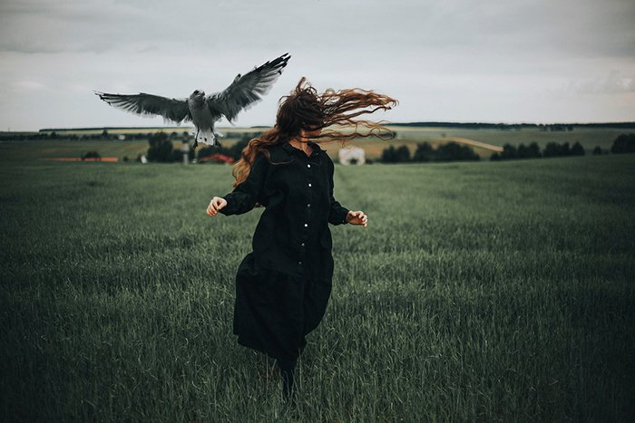 Photo of a woman running on a field with a bird flying beside her