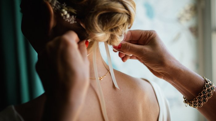 Photo of a woman adjusting a bride's headpiece