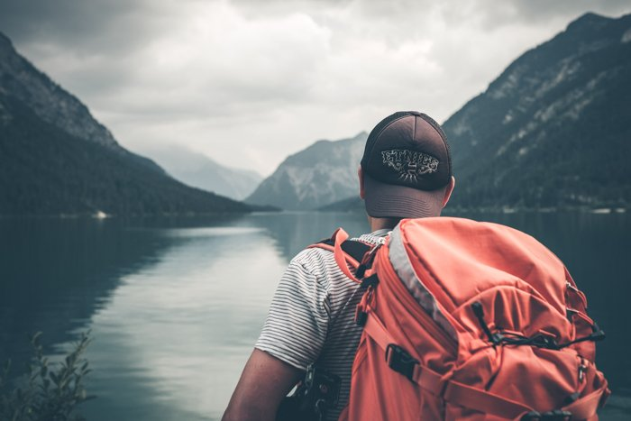 Photo of a guy with a backpack standing on the side of a lake