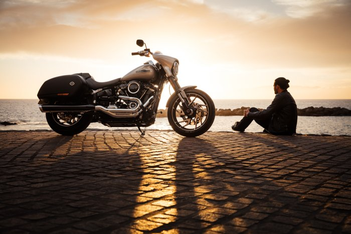 Photo of a man sitting on a seaside with a motorbike