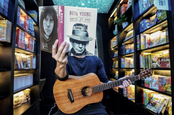 Image of a man sitting with a guitar on his lap, holding a book with a man's face on it. It looks like it was his face due to the perspective.