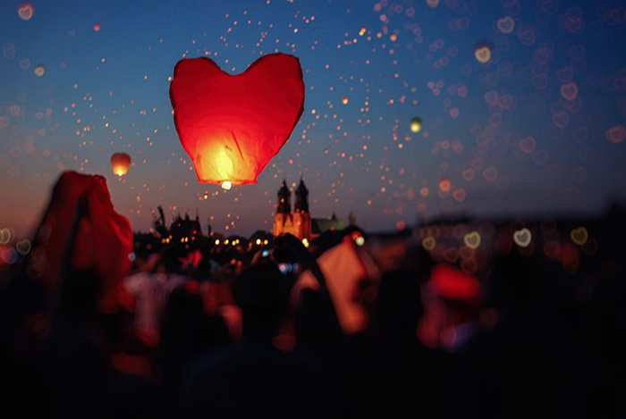 A heart shaped lantern floating into the night sky