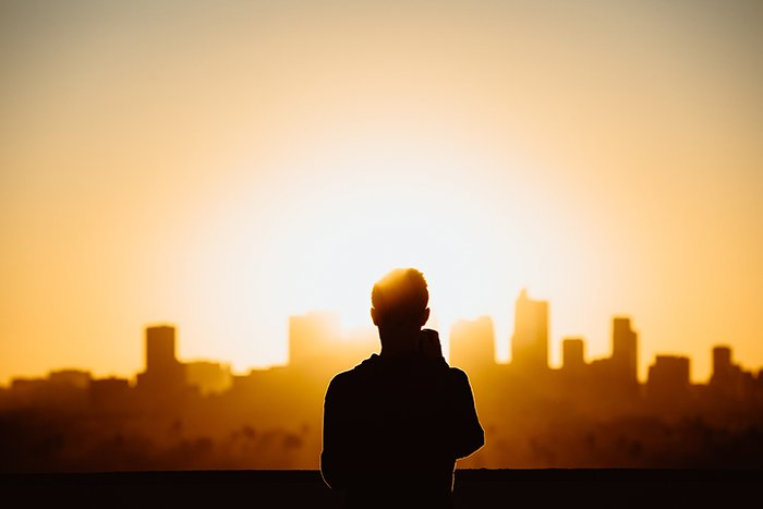 Photo of the silhouette of a man on top of a tall buinding at sunset