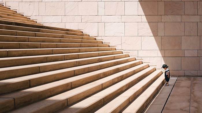 Photo of a small kid in front of a stairway with many steps