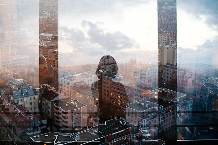 Photo of the silhouette of a woman reflecting on the window of a skyscraper