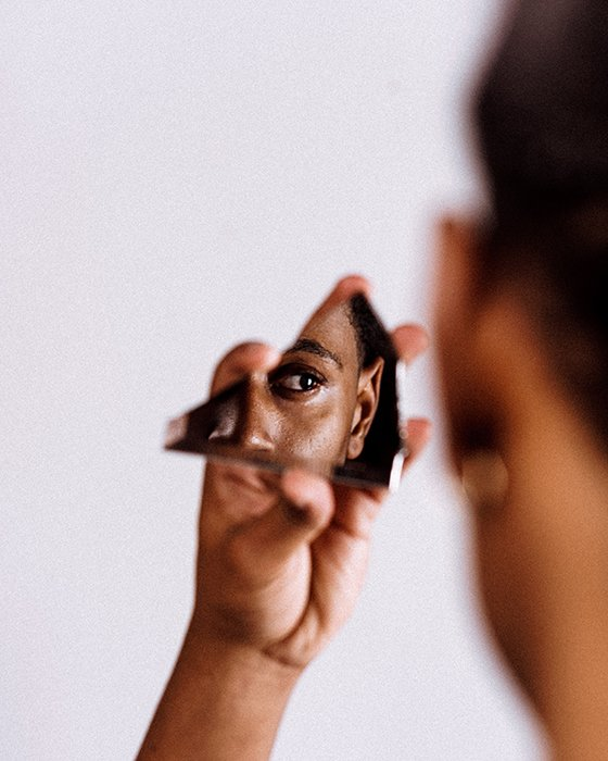 A woman's face reflecting in a broken piece of mirror