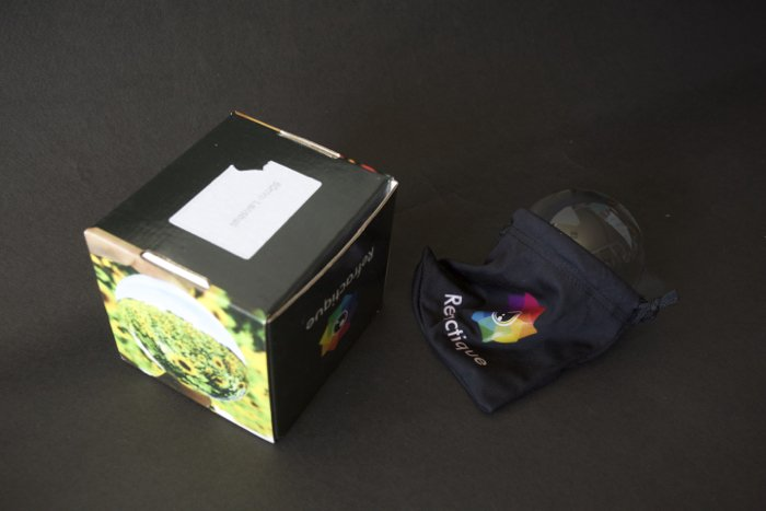 Lensballs with its Refractique logo in a case beside its packaging