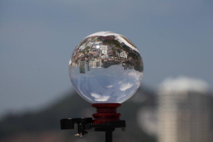 a lensball on a tripod, reflecting a sprawling cityscape