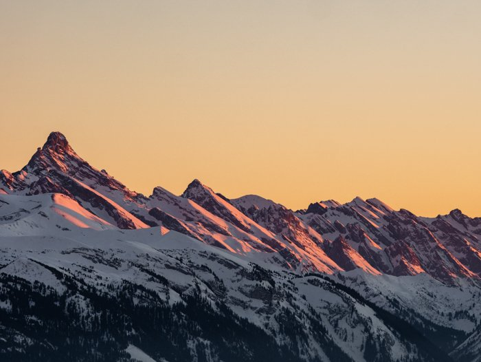 Photo of a snowy mountain range with the sky in a yellowish color