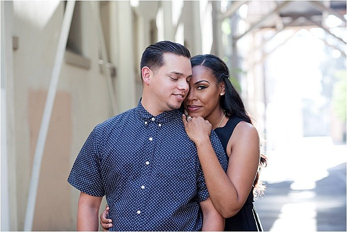 A woman hugging a man from behind during engagement photo session