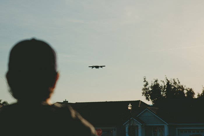 Photo of a drone flying above a house