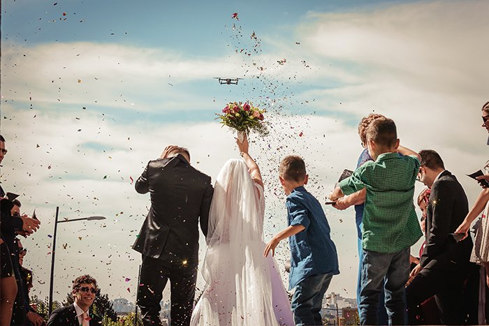 Wedding photo of the married couple and flower petals in the air