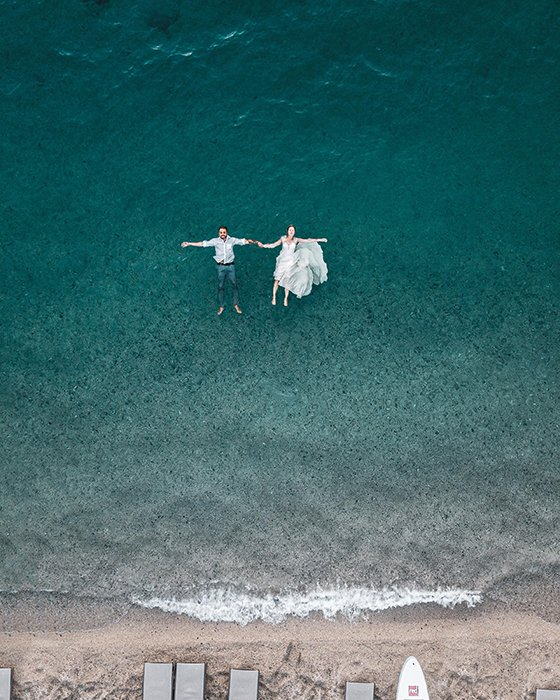 Drone wedding photo with the couple floating on the sea