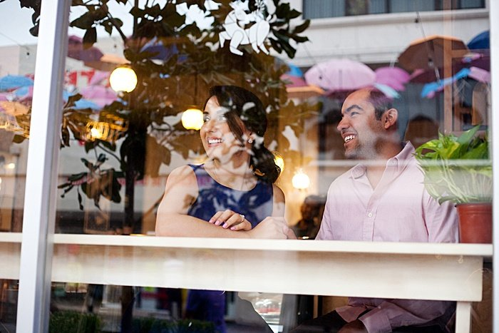 a couple smiling at a cafe window