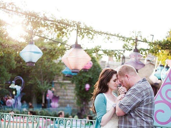 A couple kissing each others hands surrounded by lanterns highlighting engagement photo poses