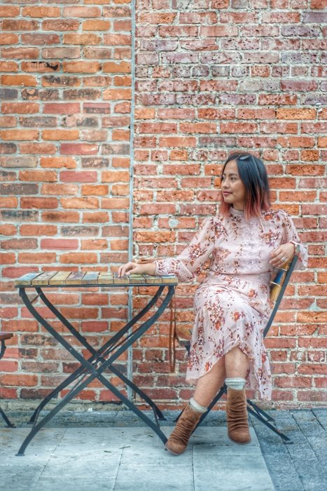Photo of a woman sitting in front of a brick wall