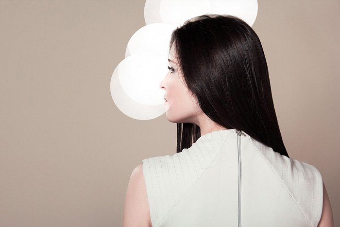 a female fashion model posing in front of a clean beige background
