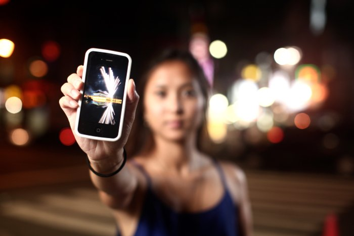 a girl holding up an iPhone outdoors at night