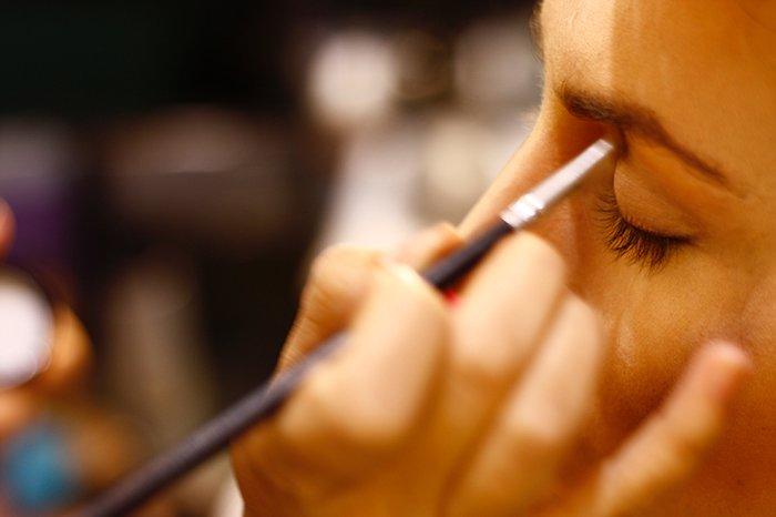 Photo of a hand applying eyeshadow on a model