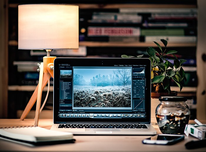 Photo of a laptop on a desk with a lamp behind it