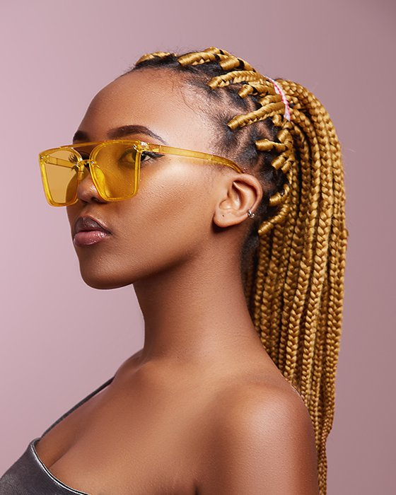 Portrait photo of a woman with yellow glasses and braided hair