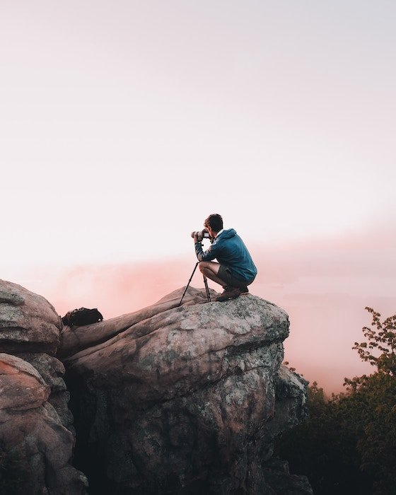 A photographer taking a photo on a cliff