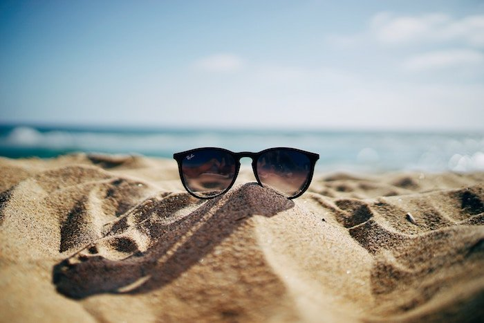 Photo of sunglasses shot on the beach in the sand