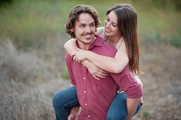 portrait of a couple trying the piggy back engagement photo poses outdoors