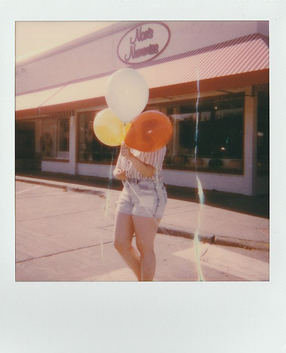 Polaroid picture of a woman with balloons in her hands