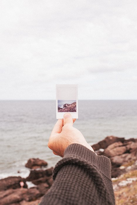 Photo of a hand holding a Polaroid picture of a beach