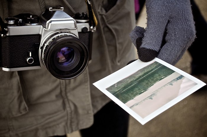 Photo of a photographer holding a Polaroid picture