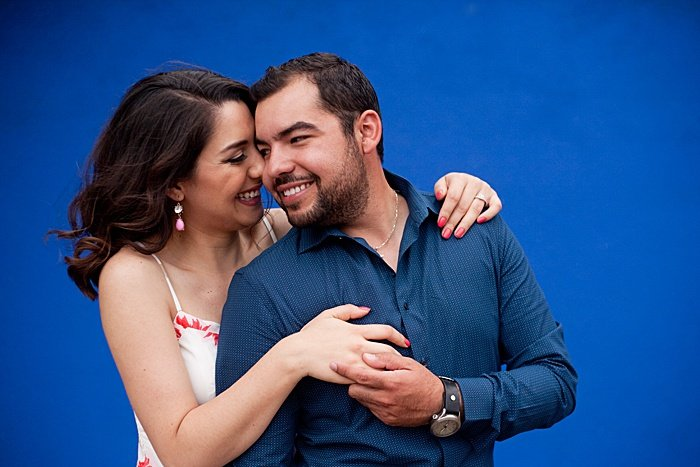 a romantic portrait of a couple trying engagement photo poses against a blue background